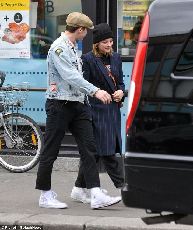 Stylish:The 20-year-old Kick Ass star looked chic in a long striped buttoned coat, covering her blonde locks under a dark beanie