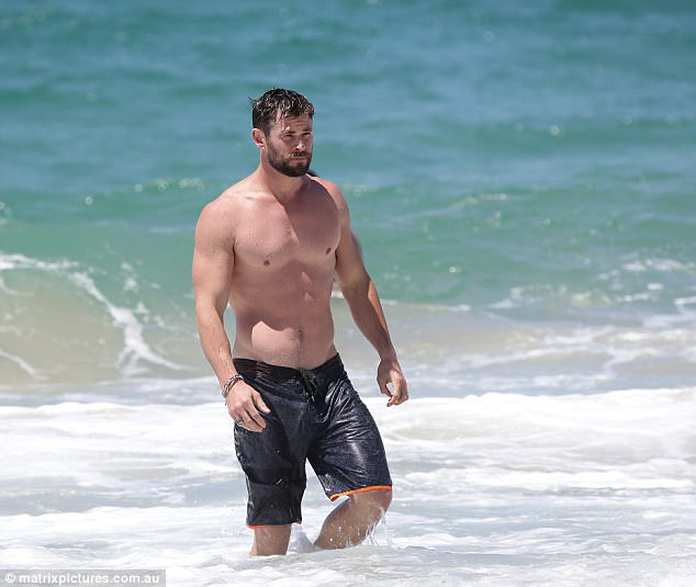 Beach buff! Stripping down to black boardshorts, Chris flaunted his bulging biceps and washboard abs as he hit the water