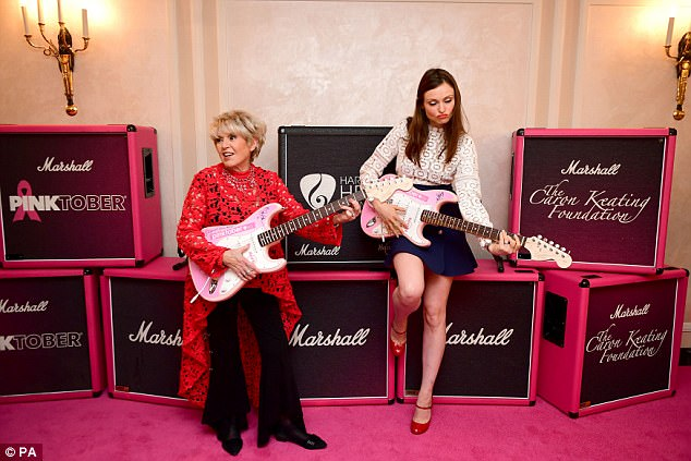 Rock chicks:The pair posed with pink guitars, appearing to be in high spirits as they stood against the backdrop of black boxes