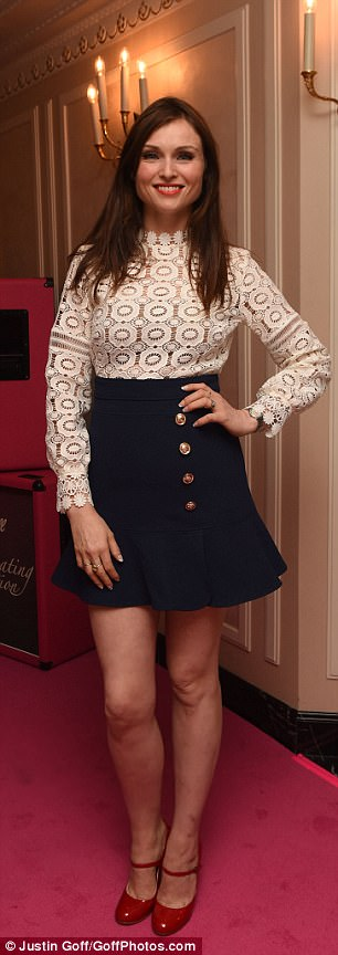 Adorned:Her top consisted of white lace flowers with long sleeves, and she donned a navy flip skirt with gold button accents