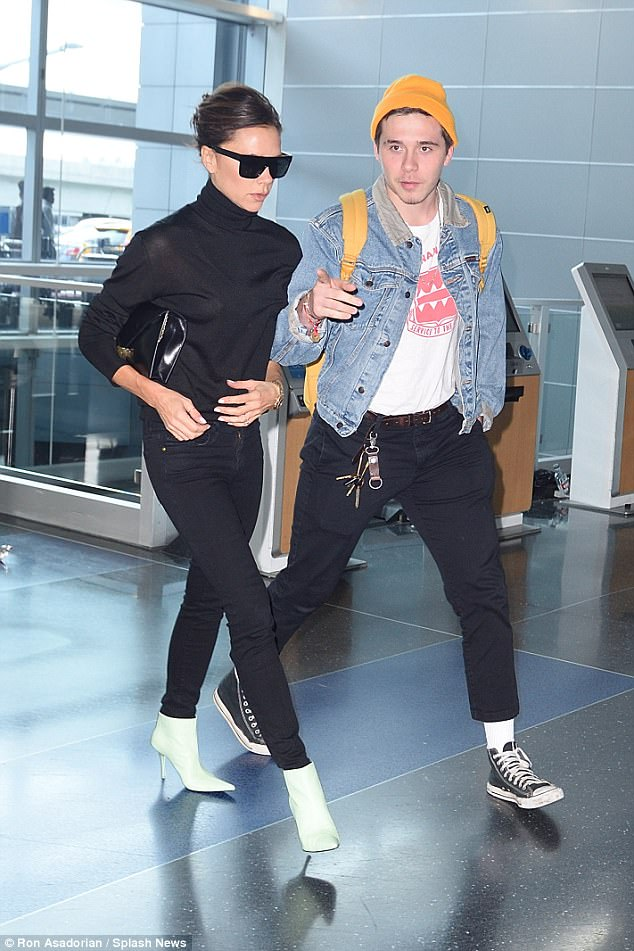 Family time:The fashion designer, 43, looked typically chic in a poloneck and pastel green boots as she arrived at the terminal with her 19-year-old son - who is currently studying in the Big Apple