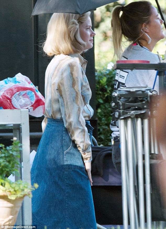 Seventies style: Adams, 43, sported a patterned blouse tucked into a denim skirt