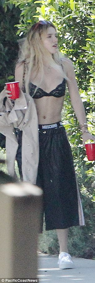Party to go: The actress snuck out carrying a plastic beverage cup in each hand