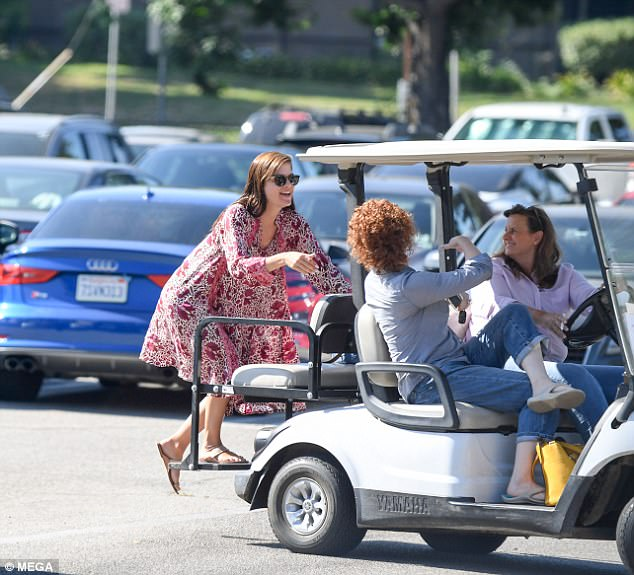 Hitching a ride: Selma had been spotted the previous day in a sunlit parking lot, smiling as she clambered onto the back of a golf cart with two other women sitting in the front