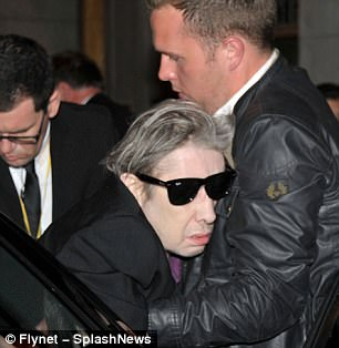 Support: The music icon appeared a little frail in his wheelchair as he was given a helping hand into an awaiting car on the way home