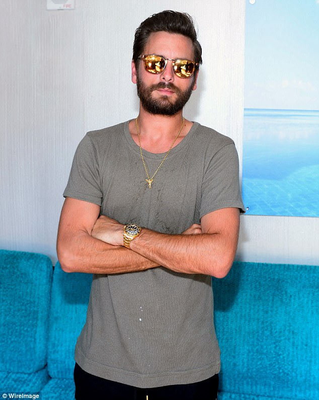 Covered up: Seemingly staying out of the water, Scott donneda grey T-shirtand reflective sunglasses at the party