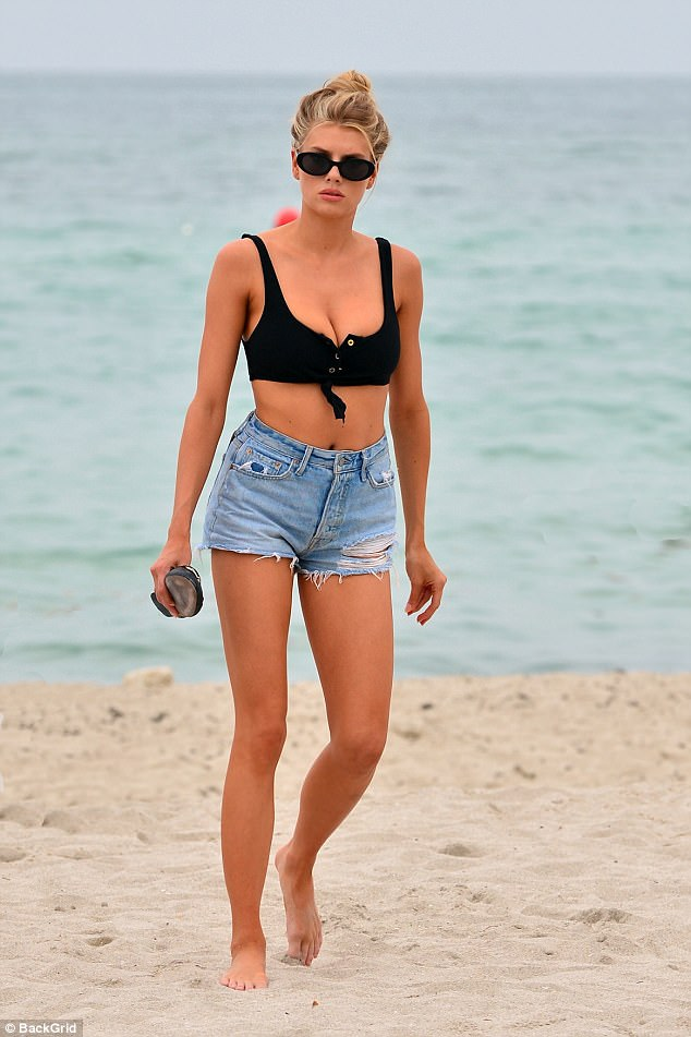 Sand stunner:Charlotte had left little to the imagination during an outing at Miami beach on Saturday as she sported a black bikini top and distressed Daisy Dukes