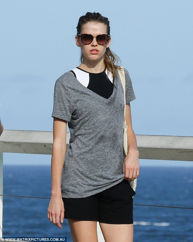 Victoria turned out to the beach in a light grey V-necked shirt over her bikini and a pair of black shorts