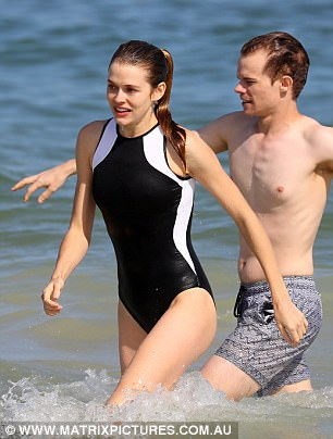 Family fun: She was soon joined by brother Alex, who looked every bit the casual beach Aussie in a plain white T-shirt and grey boardshorts, while carrying a backpack on his shoulders and a pair of trainers in his hand