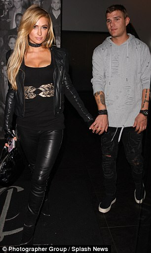 All eyes on her: Paris rocked an edgy ensemble - teaming her racy trousers with a leather biker jacket and matching fingerless gloves