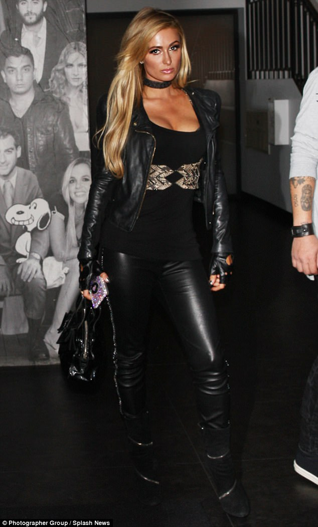 Biker chick chic:The blonde bombshell, 36, looked sensational for the outing, as she slipped into a pair of skin-tight leather trousers while stealing a look at her ample assets