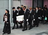Kim's sister holds a picture of the late singer, while six fellow singers carry out his coffin