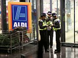 Police officers stand guard outside the Aldi in Skipton, North Yorks, where a woman was attacked with a knife