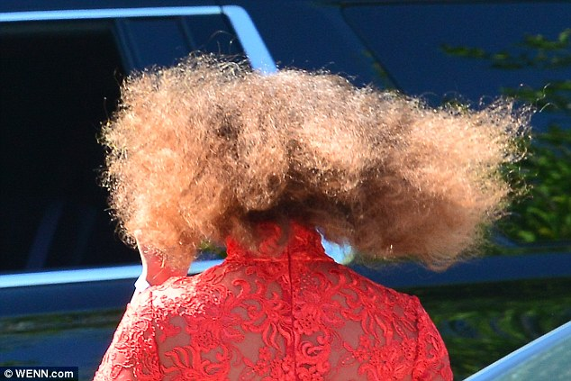 Windswept: She then maintained her natural look by leaving her hair in its everyday afro curled state - which blew back glamorously in the breeze