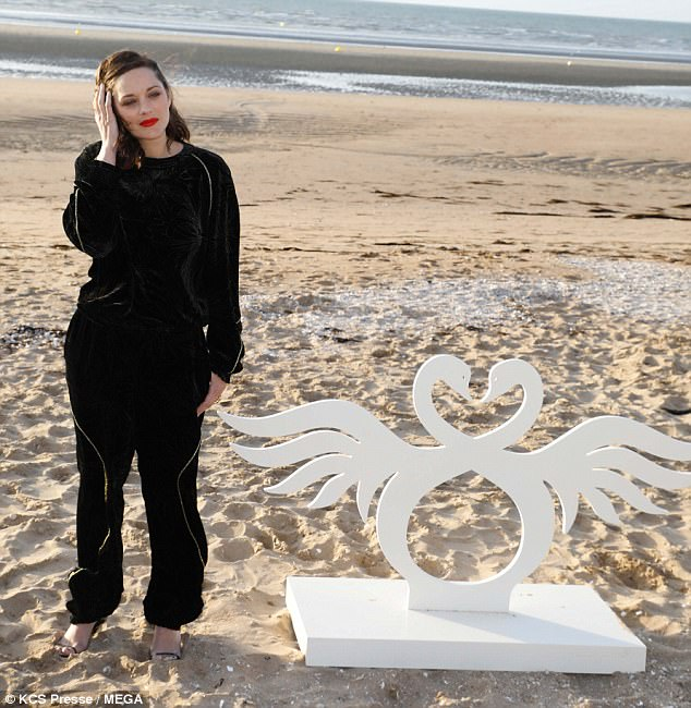 Casual glamour:The star opted for a sports luxe look for her photocall in a quirky black velour tracksuit with glittery gold flower detailing and metallic trim