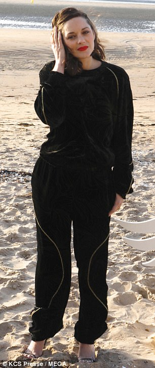 Slanted:Falling victim to the folly of the beach, the Artist star's strappy heels also perilously sunk into the sand, giving her an awkward slant as she posed up with fellow French stars