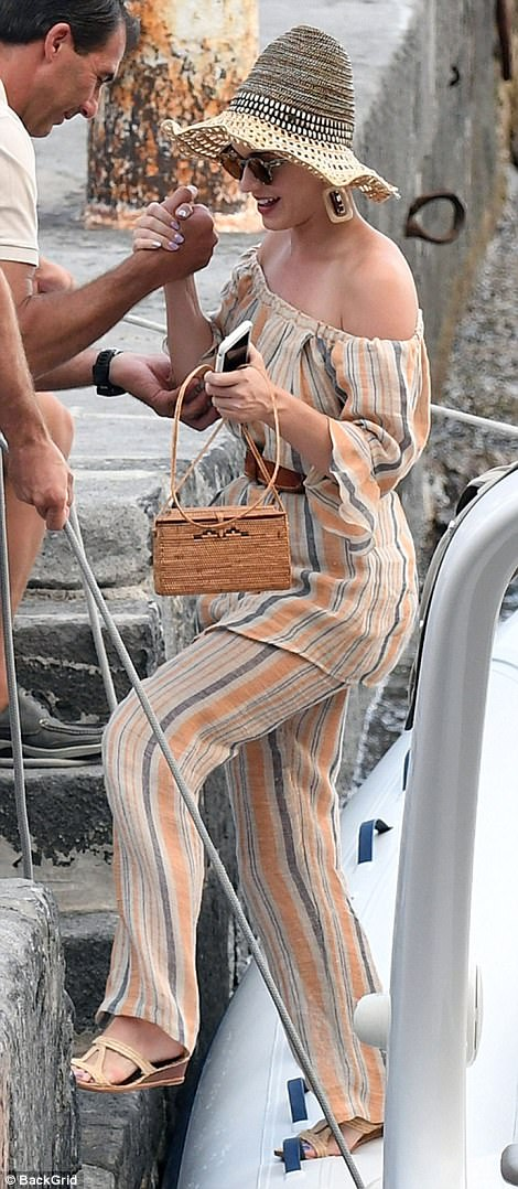 On trend: The singer looked stylish in a striped off the shoulder blouse and matching summer trousers