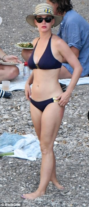 On dry land: Katy commanded attention while adjusting her sunglasses before making her way across the modest beach