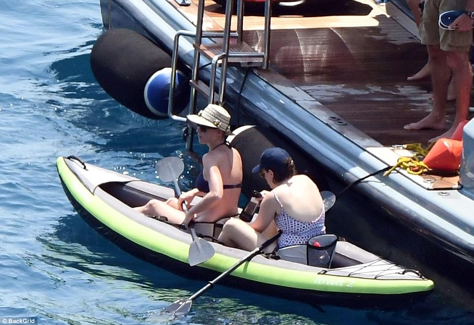 Cruise control: The pair idled close to a larger boat, with Katy sitting in front