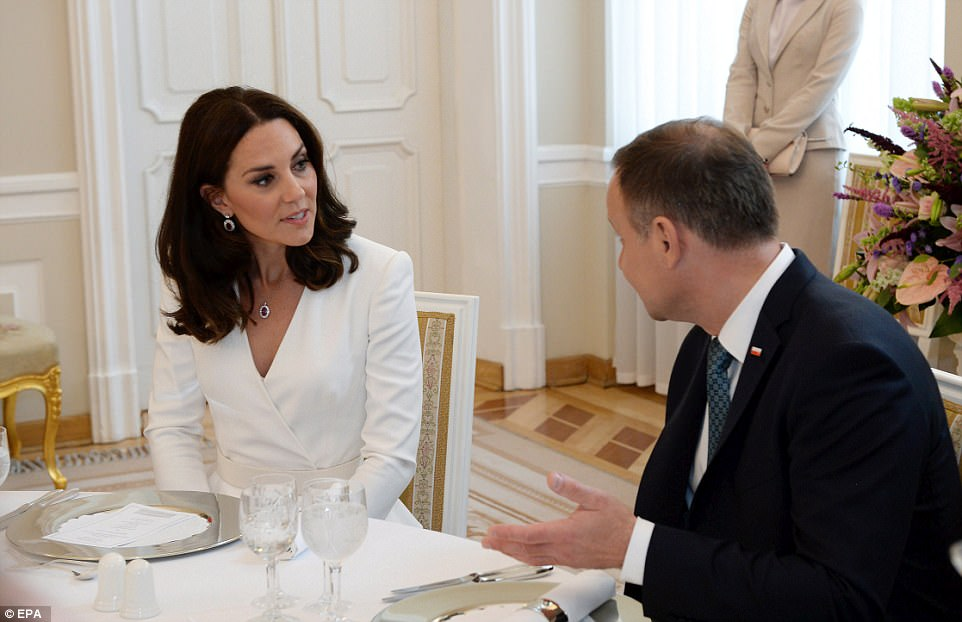 Polish President Andrzej Duda chats to the Duchess of Cambridge during an official welcome lunch. The Duchess teamed her Alexander McQueen ensemble with a pair of dazzling drop earrings and a matching necklace, but travelled without a bag