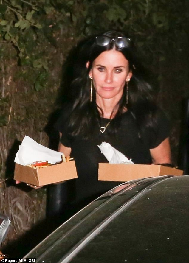Stylish: Jennifer's Friends co-star and best pal Courteney was super minimal in a black T-shirt while sporting a pair of glasses sat atop her head pushing back her raven locks