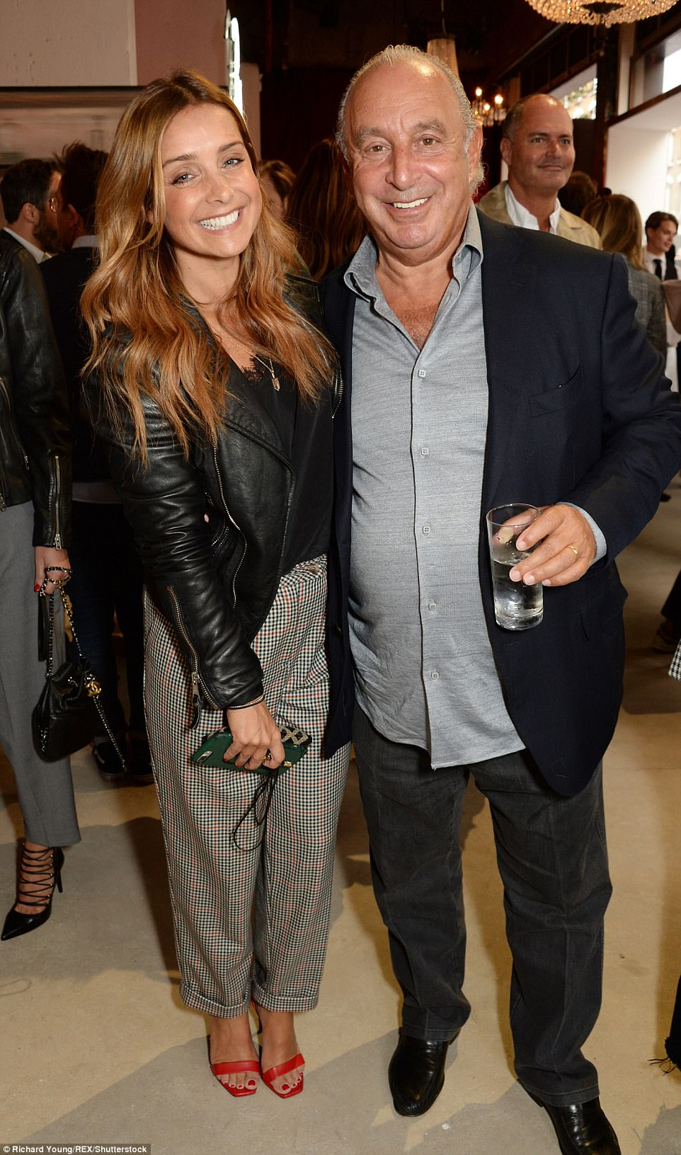 Check her out!Meanwhile Louise, 42, looked typically trendy in a pair of checked trousers and bright red heels as she posed with Sir Philip Green (R)