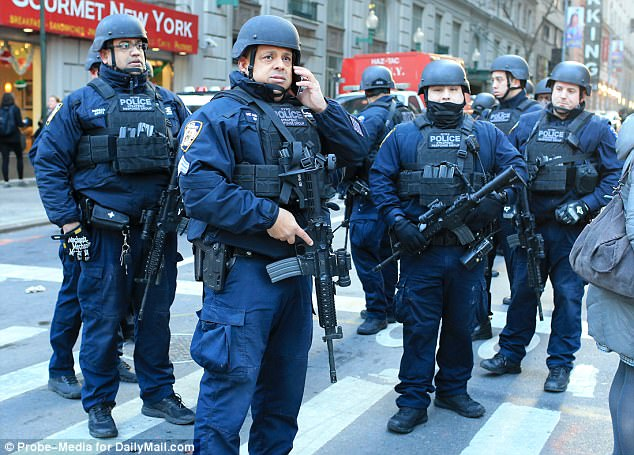 Armed NYPD officers at the scene on Monday morning await instruction after the suspect was taken away