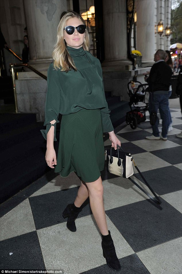 Dressed to impress:The model, 25, showed off her toned legs in a flirty moss green skirt, which she teamed with a high-necked silk top in the same shade