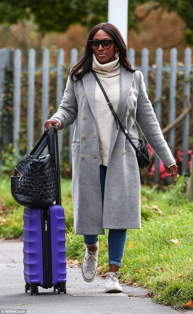 Wrapping up: The 29-year-old kept it chic in a masculine tailored grey coat and white poloneck sweater teamed with fresh white Converse sneakers