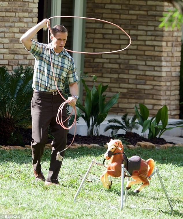 Target: The Golden Globe winner - who turns 37 in two weeks - roped a retro horseback riding toy while clad in clean-cut, conservative fifties/sixties attire on the lawn of a house