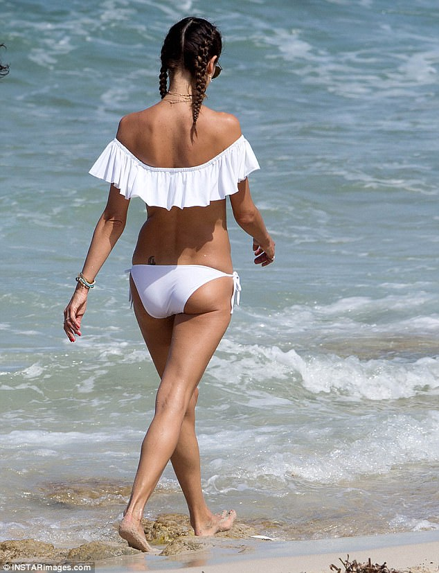 For a quick dip: The mother of two had no qualms about showing off her perky derriere or her sculpted back in the flirty beach wear