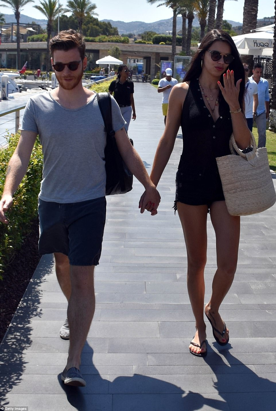 Sun-drenched: Metin threw a plain grey t-shirt over his torso and seemed delighted to be in the company of his new love