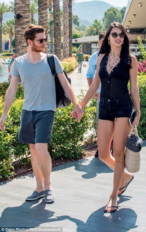 Lovely: She was seen clutching onto Metin's hand as they strolled along the marina, sporting their similar sunglasses