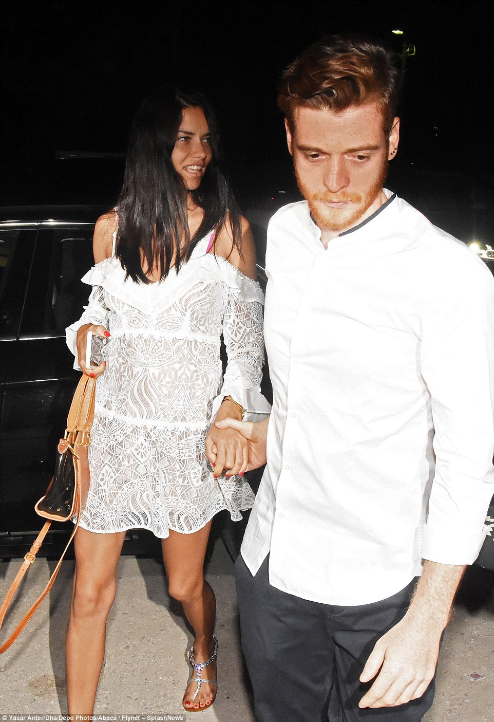 Chic: She slipped into a semi-sheer lacy white dress for their dinner date that teased a look at her slender frame underneath and made for a leggy display
