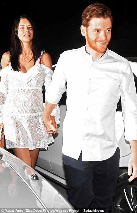 Hand-in-hand: The starlet was seen beaming from ear-to-ear as she clutched onto Metin's hand on their arrival to the eatery
