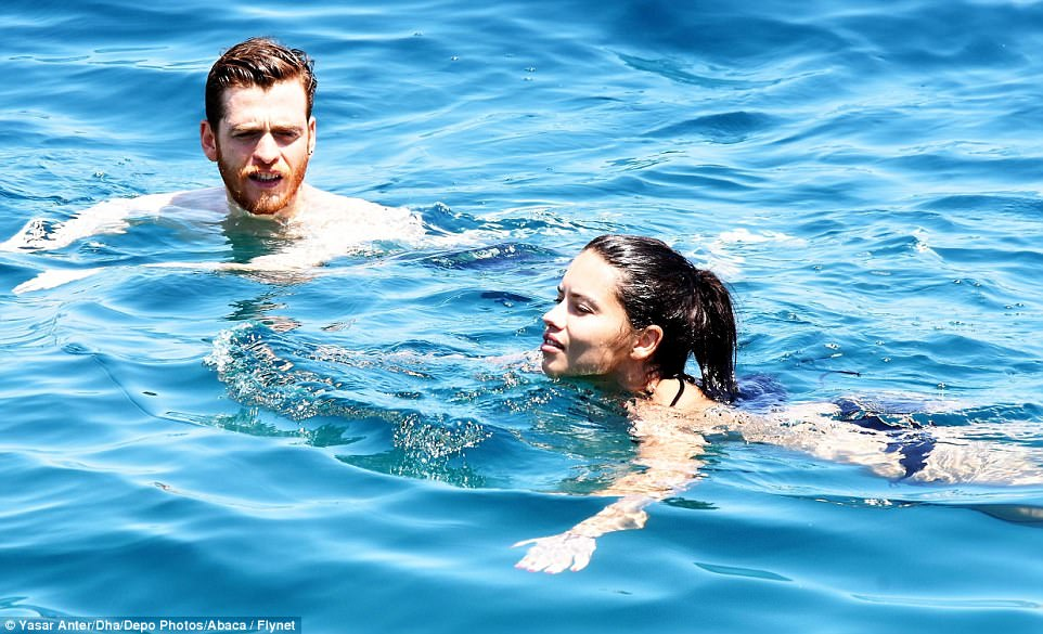 Loved-up: She and her beau Metin (pictured swimming above) initially met in June and their romance has been heating up ever since