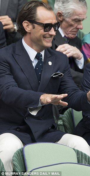 Having a ball: Jude was seen throwing his head back in delight as he shared a joke in the stands