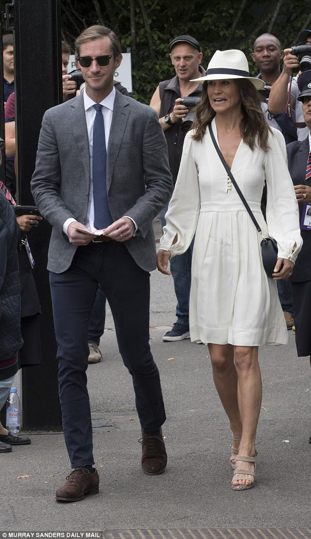 Chic: Pippa Middleton, meanwhile, cut an elegant figure in a chic cream dress  and a complementing monochrom fedora hat alongside husband James Matthews