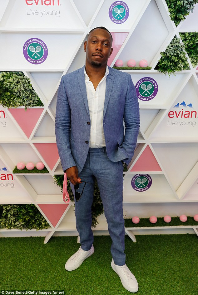 And pose: Rapper Dizzee Rascal stopped by the Evian Live Young Suite in a pale blue suit and open white shirt
