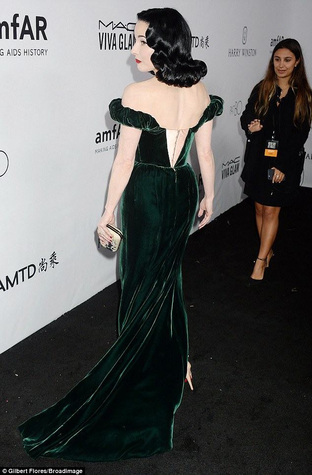 Green with envy:Her alabaster complexion stood out boldly against her trademark raven-coloured tresses while her make-up was flawlessly applied