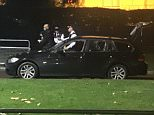 Police stand guard next to the BMW shortly after a controlled explosion was carried out