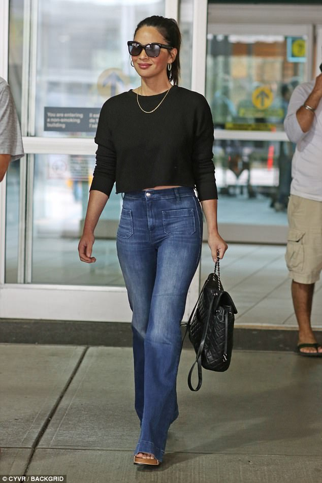Chic peek: The beauty revealed a peek at her enviable abs as she sported a cropped sweater and skin tight jeans