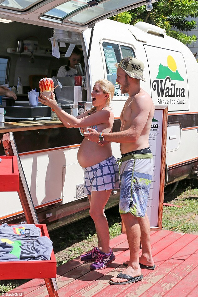 Fun in the sun:The reality star, 30, looked radiant as she put her changing shape on display in an aqua and orange palm-print bikini top and blue and white checked shorts