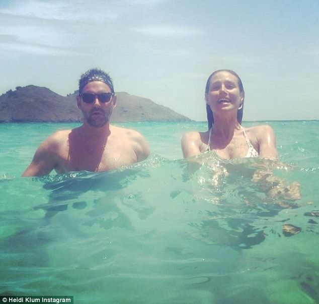 Fun in the sun: The German catwalk queen, 44, displayed her toned physique in a tiny string bikini as she jumped for joy in the ocean with a male friend while soaking up the Caribbean sun