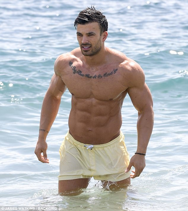 Splash-tastic:With summer temperatures soaring, the shorts-clad TV personality waded into the sea for a welcome dip