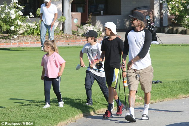 Family fun: David Beckham proved he's equally as gifted with other sports as he took daughter Harper, six, and sons Romeo, 14, and Cruz, 12, out golfing on Friday