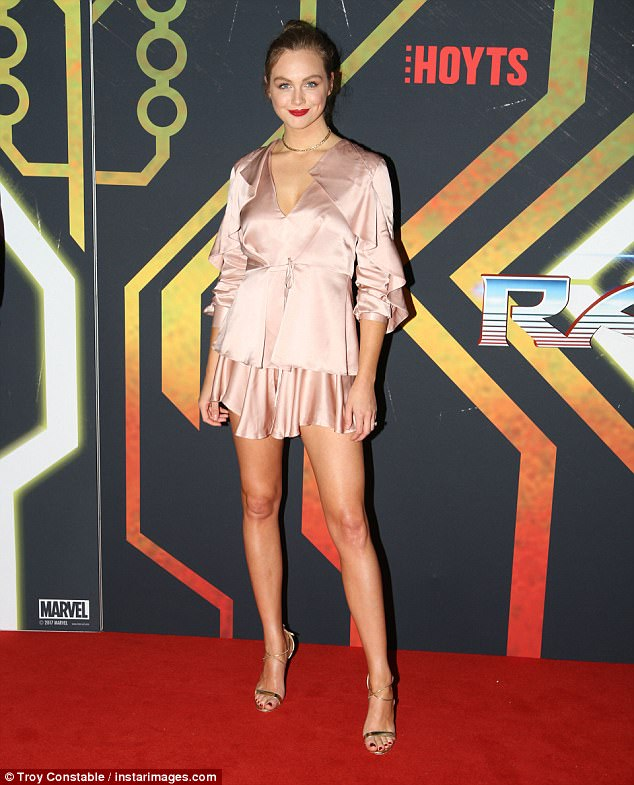 Leggy lady: The brunette opted for a pink silk frock, the hemline finishing mid-thigh, and accessorised with gold strappy heels and a delicate necklace