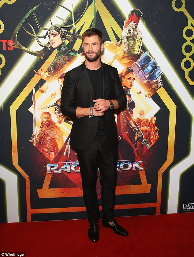 Star arrival: Chris happily posed for photos in front of the media wall at Fox Studios