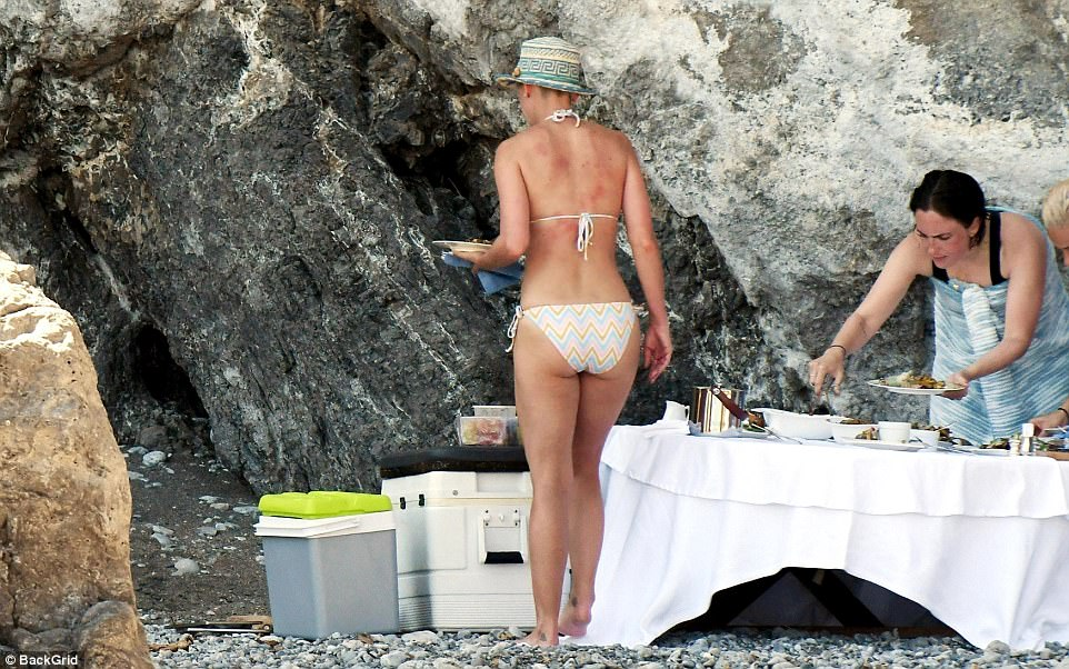 Hungry:Fit for a singing superstar, there was a lavish buffet served up on the beach with the star's friends seen helping themselves to the barbecue