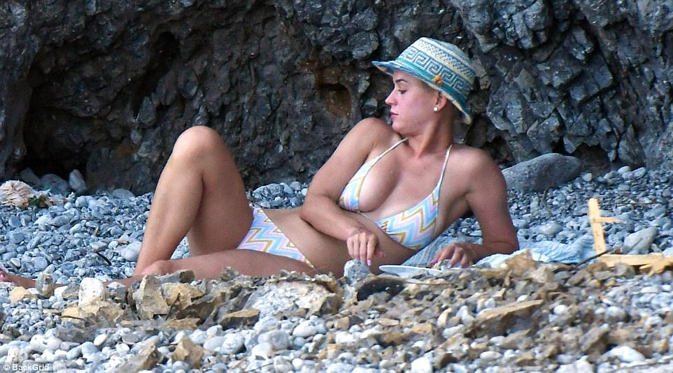 Check you out: Katy appeared to be checking out her tan as she flashed some major cleavage in her string bikini